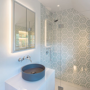 This is an example of a contemporary bathroom in London with flat-panel cabinets, white cabinets, an alcove shower, grey tiles, white walls, a vessel sink, grey floors, a hinged door, white worktops, a single sink, a floating vanity unit and a vaulted ceiling.