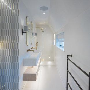 Idéer för att renovera ett funkis vit vitt badrum, med släta luckor, skåp i ljust trä, en kantlös dusch, vit kakel, vita väggar, ett avlångt handfat, vitt golv och dusch med gångjärnsdörr