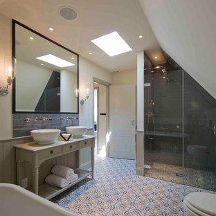 На фото: главная ванная комната среднего размера в классическом стиле с фасадами островного типа, бежевыми фасадами, ванной на ножках, открытым душем, унитазом-моноблоком, серой плиткой, керамической плиткой, бежевыми стенами, полом из мозаичной плитки, раковиной с пьедесталом, столешницей из дерева, разноцветным полом, душем с распашными дверями и белой столешницей