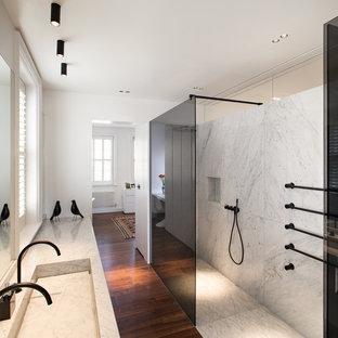 Foto di una stanza da bagno padronale contemporanea con doccia a filo pavimento, pistrelle in bianco e nero, piastrelle di marmo, pareti bianche, parquet scuro, lavabo integrato, top in marmo, pavimento marrone e doccia aperta