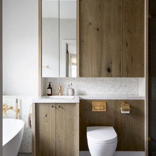 На фото: большая детская ванная комната в скандинавском стиле с фасадами с утопленной филенкой, фасадами цвета дерева среднего тона, отдельно стоящей ванной, коричневой плиткой, керамической плиткой, столешницей терраццо, серой столешницей, тумбой под одну раковину и встроенной тумбой