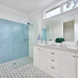 Photo of a beach style 3/4 bathroom in Melbourne with shaker cabinets, beige cabinets, an alcove shower, blue tile, beige walls, a drop-in sink, grey floor, an open shower and grey benchtops.