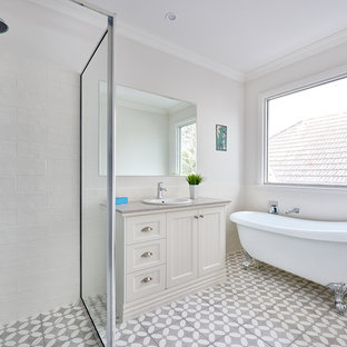 This is an example of a beach style 3/4 bathroom in Melbourne with shaker cabinets, beige cabinets, a claw-foot tub, a corner shower, a drop-in sink, grey floor, a hinged shower door and grey benchtops.
