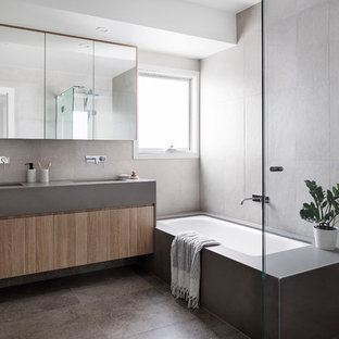 Contemporary kids bathroom in Melbourne with flat-panel cabinets, light wood cabinets, an undermount tub, a corner shower, beige tile, porcelain tile, white walls, porcelain floors, an undermount sink, engineered quartz benchtops, grey floor, a hinged shower door and grey benchtops.