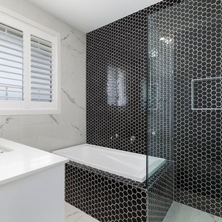 Photo of a contemporary 3/4 bathroom in Brisbane with a corner tub, a corner shower, black tile, an undermount sink and a hinged shower door.