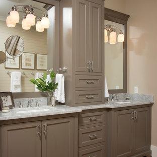 Imagen de cuarto de baño principal, campestre, de tamaño medio, con lavabo bajoencimera, armarios con paneles empotrados, paredes grises, suelo de madera en tonos medios, encimera de mármol y puertas de armario marrones