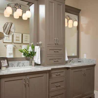 Mid-sized country master medium tone wood floor bathroom photo in Charleston with an undermount sink, recessed-panel cabinets, gray walls, marble countertops and brown cabinets