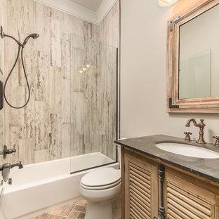 Ispirazione per una stanza da bagno industriale di medie dimensioni con ante a persiana, ante in legno chiaro, vasca ad alcova, vasca/doccia, WC a due pezzi, piastrelle grigie, piastrelle in gres porcellanato, pareti grigie, pavimento in mattoni, lavabo sottopiano e top in cemento