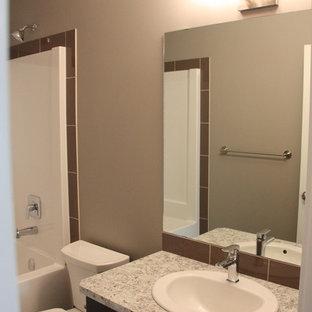 Foto di una piccola stanza da bagno per bambini american style con lavabo da incasso, ante lisce, ante marroni, top in laminato, vasca da incasso, vasca/doccia, WC monopezzo, piastrelle marroni, piastrelle in ceramica, pareti grigie e pavimento in linoleum