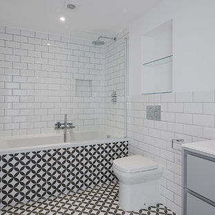 This is an example of a small modern family bathroom in London with flat-panel cabinets, grey cabinets, a built-in bath, a shower/bath combination, a one-piece toilet, white tiles, metro tiles, white walls, porcelain flooring, a built-in sink, black floors and a hinged door.