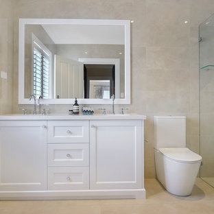 Photo of a large traditional 3/4 bathroom in Sydney with shaker cabinets, white cabinets, a curbless shower, a two-piece toilet, beige tile, an undermount sink, beige floor and white benchtops.