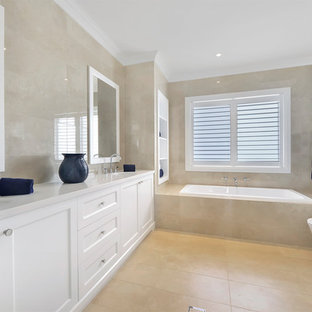 Inspiration for a large traditional 3/4 bathroom in Sydney with shaker cabinets, white cabinets, a drop-in tub, a corner shower, beige tile, an undermount sink, beige floor, a hinged shower door and white benchtops.
