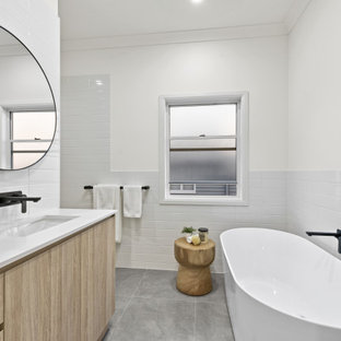 This is an example of a mid-sized contemporary kids bathroom in Brisbane with a freestanding tub, white tile, subway tile, white walls, porcelain floors, an undermount sink, engineered quartz benchtops, a hinged shower door, white benchtops, flat-panel cabinets, light wood cabinets and grey floor.