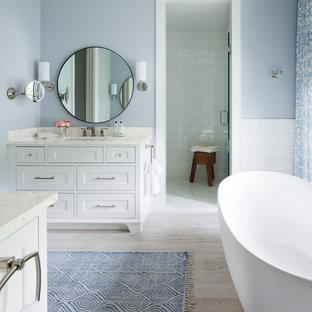 Modelo de cuarto de baño principal, costero, sin sin inodoro, con armarios con paneles empotrados, puertas de armario blancas, bañera exenta, baldosas y/o azulejos blancos, paredes azules, lavabo bajoencimera, suelo beige y ducha con puerta con bisagras