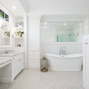 Beach style master bathroom in Gold Coast - Tweed with recessed-panel cabinets, white cabinets, a freestanding tub, a corner shower, white tile, subway tile, white walls, mosaic tile floors, an undermount sink, marble benchtops, white floor, a hinged shower door and grey benchtops.