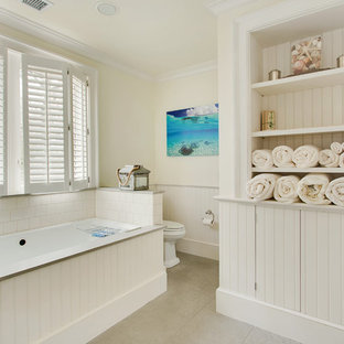 Beach style bathroom in New York with open cabinets, a submerged bath and beige walls.