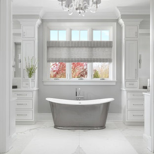 Example of a large classic master marble floor and white floor freestanding bathtub design in St Louis with white walls, beaded inset cabinets and white cabinets