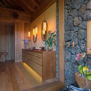 Esempio di una stanza da bagno padronale tropicale con ante lisce, ante in legno chiaro, pareti beige, pavimento in legno massello medio, lavabo rettangolare e top in legno