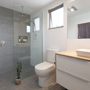 Alcove shower - small modern master gray tile and ceramic tile ceramic floor alcove shower idea in Perth with a drop-in sink, white cabinets, wood countertops and white walls