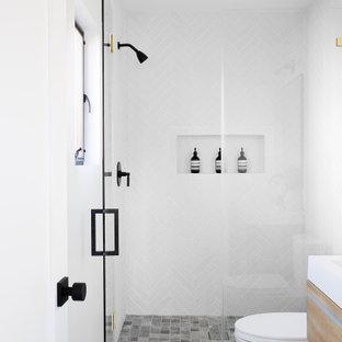 Idéer för att renovera ett litet funkis vit vitt badrum med dusch, med släta luckor, skåp i mellenmörkt trä, en dusch i en alkov, en toalettstol med hel cisternkåpa, vita väggar, betonggolv, ett integrerad handfat, bänkskiva i akrylsten, grått golv och dusch med gångjärnsdörr