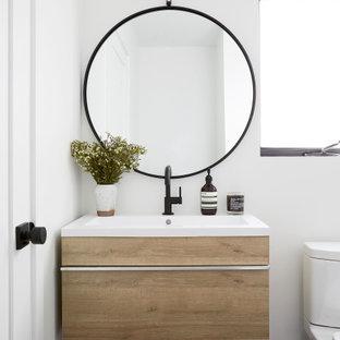 Foto de cuarto de baño con ducha, actual, pequeño, con armarios con paneles lisos, puertas de armario de madera clara, sanitario de dos piezas, paredes blancas, suelo de baldosas de cerámica, encimera de acrílico, suelo negro, encimeras blancas y lavabo tipo consola