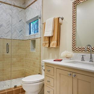 Immagine di una stanza da bagno con doccia classica con ante con riquadro incassato, ante gialle, doccia alcova, piastrelle bianche, piastrelle gialle, pareti beige, pavimento con piastrelle a mosaico, lavabo sottopiano, pavimento grigio e porta doccia a battente