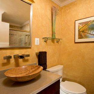 Esempio di una piccola stanza da bagno classica con lavabo a bacinella, ante a persiana, ante in legno scuro, doccia alcova, piastrelle beige, piastrelle in ceramica, pareti gialle, parquet scuro, top in granito e WC a due pezzi