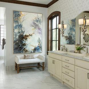 Immagine di una grande stanza da bagno padronale classica con ante con bugna sagomata, ante gialle, pareti grigie, pavimento in marmo, lavabo da incasso e top in marmo