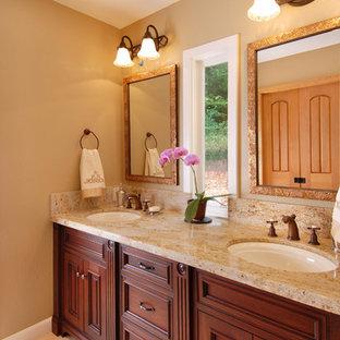 Modelo de cuarto de baño principal, clásico, de tamaño medio, con lavabo bajoencimera, puertas de armario de madera en tonos medios, encimera de granito, ducha abierta, baldosas y/o azulejos beige, baldosas y/o azulejos de piedra, armarios con paneles con relieve y encimeras beige