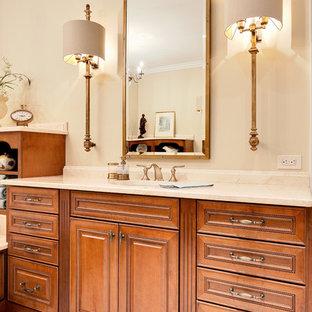 アトランタの巨大なトラディショナルスタイルのおしゃれなマスターバスルーム (レイズドパネル扉のキャビネット、中間色木目調キャビネット、ドロップイン型浴槽、コーナー設置型シャワー、分離型トイレ、ベージュの壁、磁器タイルの床、アンダーカウンター洗面器、大理石の洗面台、ベージュの床、開き戸のシャワー、ベージュのカウンター、トイレ室、洗面台2つ、造り付け洗面台) の写真