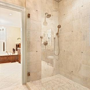 Пример оригинального дизайна: огромная главная ванная комната в классическом стиле с фасадами с выступающей филенкой, фасадами цвета дерева среднего тона, накладной ванной, угловым душем, раздельным унитазом, бежевой плиткой, бежевыми стенами, полом из керамогранита, врезной раковиной, мраморной столешницей, бежевым полом, душем с распашными дверями, бежевой столешницей, унитазом, тумбой под две раковины и встроенной тумбой