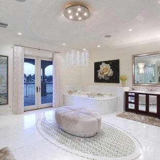 На фото: огромная главная ванная комната в средиземноморском стиле с врезной раковиной, стеклянными фасадами, темными деревянными фасадами, столешницей из гранита, накладной ванной, открытым душем, бежевой плиткой, керамической плиткой, бежевыми стенами и мраморным полом с
