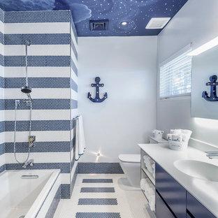 マイアミの小さいコンテンポラリースタイルのおしゃれな子供用バスルーム (フラットパネル扉のキャビネット、青いキャビネット、アルコーブ型浴槽、シャワー付き浴槽、一体型トイレ、マルチカラーのタイル、モザイクタイル、マルチカラーの壁、モザイクタイル、一体型シンク、人工大理石カウンター、オープンシャワー) の写真