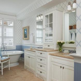 Ispirazione per una stanza da bagno per bambini costiera di medie dimensioni con lavabo sottopiano, ante di vetro, ante bianche, top in granito, vasca freestanding, pareti blu, pavimento in travertino, piastrelle beige e piastrelle in pietra