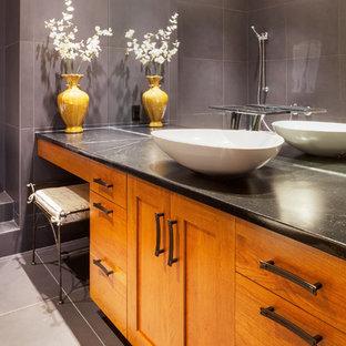 Foto de cuarto de baño principal, de estilo americano, con lavabo sobreencimera, puertas de armario de madera oscura, encimera de esteatita, baldosas y/o azulejos marrones, baldosas y/o azulejos de piedra y suelo de pizarra