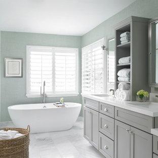 マイアミの広いトランジショナルスタイルのおしゃれなマスターバスルーム (アンダーカウンター洗面器、シェーカースタイル扉のキャビネット、グレーのキャビネット、置き型浴槽、アルコーブ型シャワー、青い壁、クオーツストーンの洗面台、白いタイル、サブウェイタイル、大理石の床、グレーの床、開き戸のシャワー) の写真