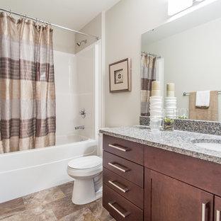 Foto de cuarto de baño con ducha, clásico renovado, pequeño, con armarios estilo shaker, puertas de armario de madera oscura, bañera empotrada, combinación de ducha y bañera, sanitario de dos piezas, paredes grises, suelo de linóleo, lavabo bajoencimera y encimera de granito