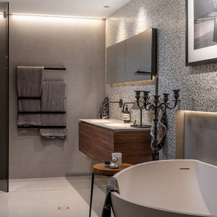 Small contemporary master bathroom in Sydney with flat-panel cabinets, dark wood cabinets, a freestanding tub, a curbless shower, gray tile, mosaic tile, grey walls, porcelain floors, an integrated sink, engineered quartz benchtops, grey floor, white benchtops and a hinged shower door.