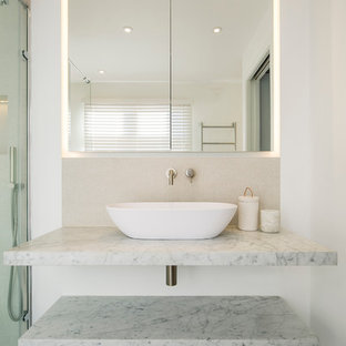Medium sized modern ensuite bathroom in London with glass-front cabinets, a freestanding bath, a corner shower, a wall mounted toilet, beige tiles, porcelain tiles, beige walls, porcelain flooring, a vessel sink and marble worktops.