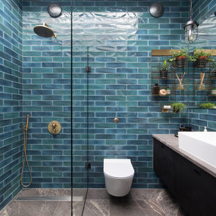 Photo of an urban shower room in London with flat-panel cabinets, black cabinets, an alcove shower, a wall mounted toilet, blue tiles, blue walls, a trough sink, brown floors and an open shower.