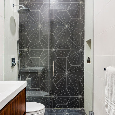 Walk-in shower - mid-sized contemporary kids' gray tile and porcelain tile porcelain tile, gray floor and single-sink walk-in shower idea in New York with flat-panel cabinets, medium tone wood cabinets, a one-piece toilet, white walls, an integrated sink, solid surface countertops, a hinged shower door, white countertops and a floating vanity