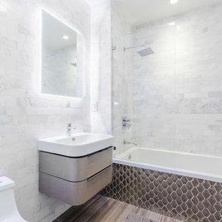 Ispirazione per una stanza da bagno nordica di medie dimensioni con consolle stile comò, ante grigie, vasca da incasso, vasca/doccia, WC monopezzo, piastrelle bianche, piastrelle di marmo, pavimento in gres porcellanato, lavabo sospeso e doccia aperta