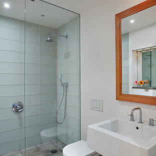 Inspiration for a contemporary blue tile and glass tile concrete floor alcove shower remodel in New York with a wall-mount sink, a wall-mount toilet and white walls