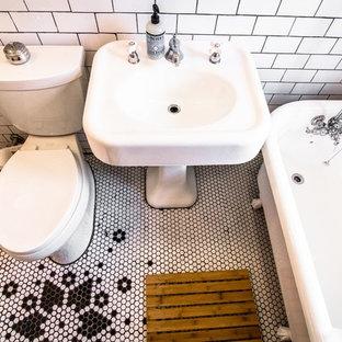 Esempio di una piccola stanza da bagno moderna con lavabo a colonna, vasca con piedi a zampa di leone, vasca/doccia, WC a due pezzi, piastrelle bianche, piastrelle in gres porcellanato, pareti beige e parquet chiaro