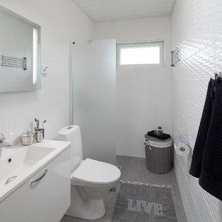 Идея дизайна: ванная комната в скандинавском стиле с плоскими фасадами, белыми фасадами, раздельным унитазом, белой плиткой, белыми стенами, душем без бортиков и серым полом