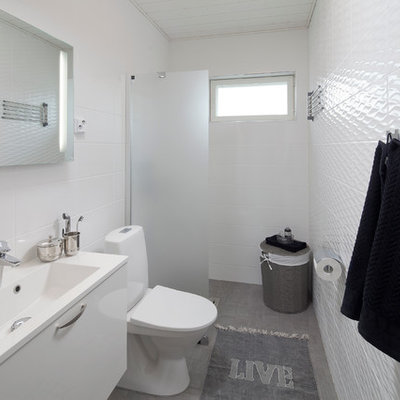 Walk-in shower - scandinavian white tile gray floor walk-in shower idea in Devon with flat-panel cabinets, white cabinets, a two-piece toilet and white walls