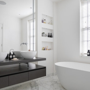 Photo of a medium sized contemporary bathroom in London with flat-panel cabinets, black cabinets, a freestanding bath, white walls, marble flooring, a vessel sink, wooden worktops and white floors.