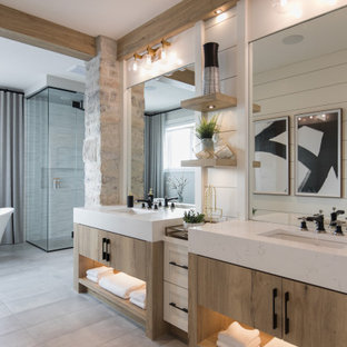 Inspiration for a huge cottage master porcelain tile porcelain floor, gray floor and shiplap wall bathroom remodel in Calgary with shaker cabinets, light wood cabinets, a one-piece toilet, white walls, an undermount sink, quartz countertops, a hinged shower door and white countertops