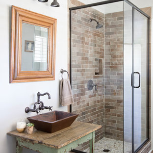 This is an example of a farmhouse family bathroom in Charleston with freestanding cabinets, a corner shower, metro tiles, grey walls, medium hardwood flooring, a vessel sink, wooden worktops, brown floors, a hinged door, brown worktops, distressed cabinets and brown tiles.