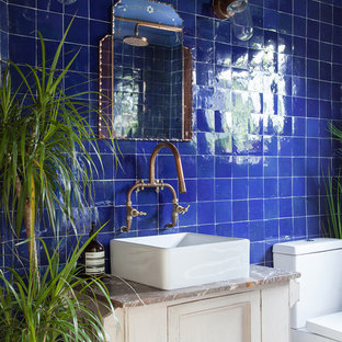 Small bohemian family bathroom in London with freestanding cabinets, beige cabinets, a freestanding bath, a shower/bath combination, a one-piece toilet, blue tiles, cement tiles, blue walls, cement flooring, a console sink, marble worktops, white floors and a shower curtain.